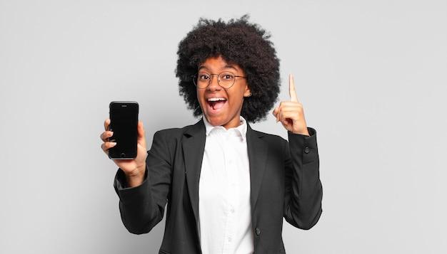 Giovane imprenditrice afro che si sente come un genio felice ed eccitato dopo aver realizzato un'idea, alzando allegramente il dito, eureka !. concetto di affari