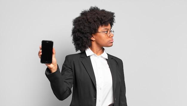 Giovane imprenditrice afro sulla vista di profilo cercando di copiare lo spazio avanti, pensare, immaginare o sognare ad occhi aperti.