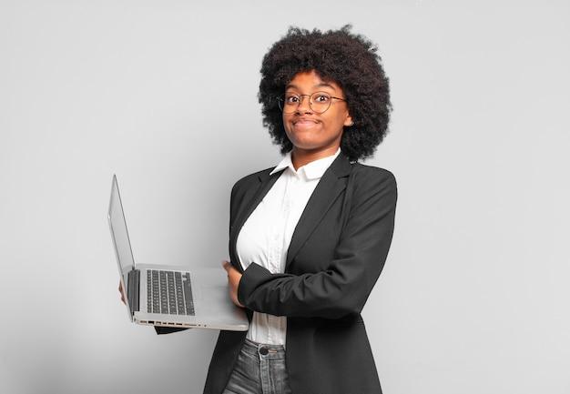 Giovane donna d'affari afro che alza le spalle