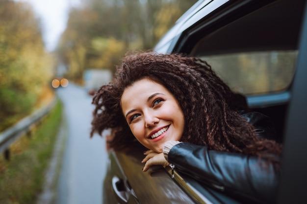 La giovane donna dei capelli afro viaggia in auto sulla strada autunnale della foresta selvaggia. lo sguardo femminile nella finestra aperta dal retro si siede con un sorriso felice.