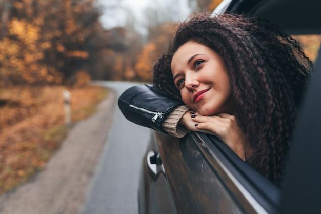 La giovane donna dei capelli afro viaggia in macchina sulla strada autunnale della foresta selvaggia e nella finestra aperta dal sedile posteriore