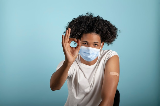 Giovane afro latino che mostra il braccio con il cerotto del vaccino contro il coronavirus con gesto ok e maschera protettiva su sfondo blu