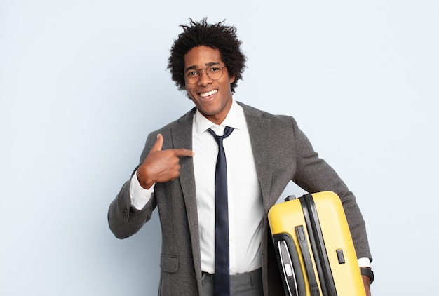 Giovane uomo afro che si sente felice, sorpreso e orgoglioso, indicando se stesso con uno sguardo eccitato e stupito