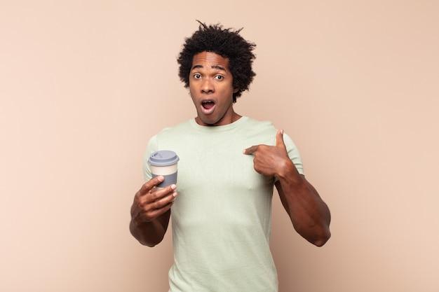 Giovane uomo afro che sembra scioccato e sorpreso con la bocca spalancata, indicando se stesso
