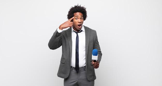 Giovane uomo afro che sembra sorpreso, a bocca aperta, scioccato, realizzando un nuovo pensiero, idea o concetto