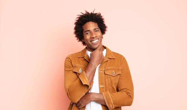 Giovane uomo afro sorridente felicemente e fantasticando o dubitando, guardando al lato