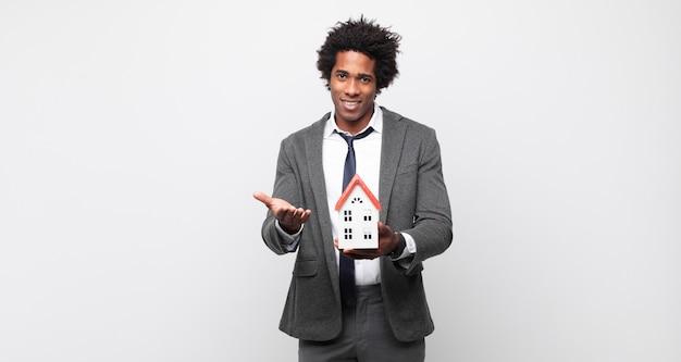 Giovane uomo afro che sorride felicemente con sguardo amichevole, fiducioso, positivo, offrendo e mostrando un oggetto o un concetto