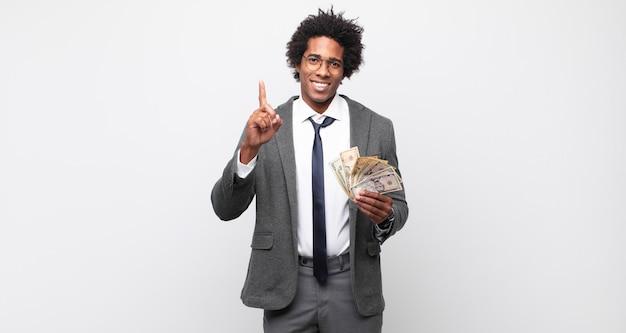 Giovane uomo afro sorridente e guardando amichevole, mostrando il numero uno o il primo con la mano in avanti, il conto alla rovescia
