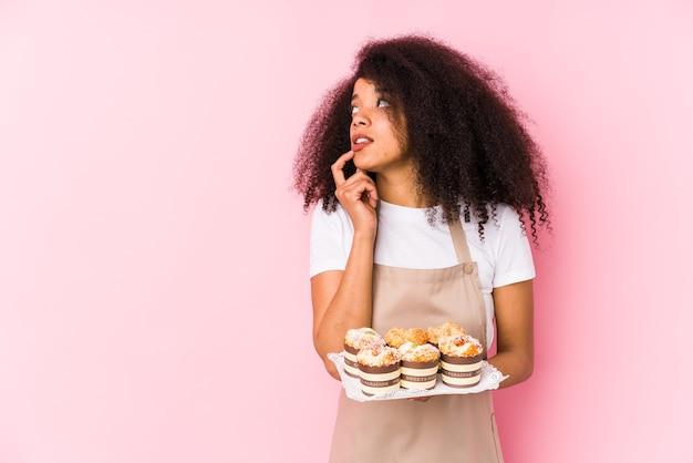 Giovane donna afro pasticcere che tiene un cupcakes isolato. la giovane donna afro baker si è rilassata pensando a qualcosa guardando uno spazio di copia.