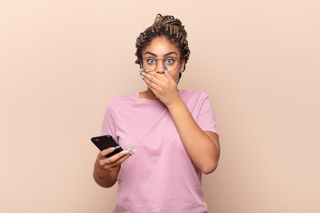 Giovane donna afro che copre la bocca con le mani con uno scioccato