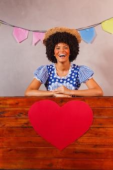 Giovane donna afro vestita per junina party dietro una tavola di legno con un cuore