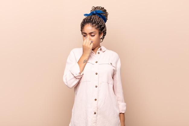 Giovane donna afro che si sente disgustata, tenendo il naso per evitare di annusare un fetore sgradevole e sgradevole