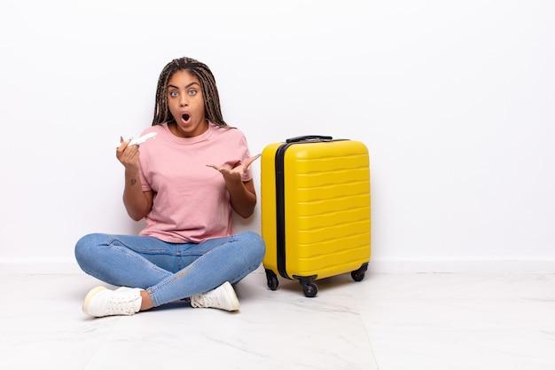 Giovane donna afro che si sente estremamente scioccata e sorpresa, ansiosa e in preda al panico, con uno sguardo stressato e inorridito. concetto di vacanze