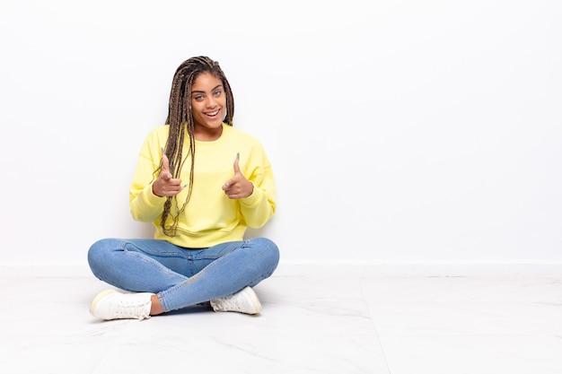 Giovane donna afro che si sente felice, fredda, soddisfatta, rilassata e di successo, punta la telecamera, sceglie te