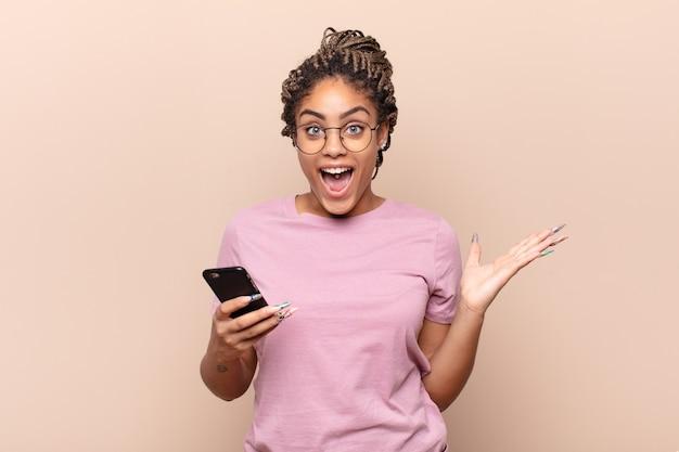 Giovane donna afro che si sente felice, eccitata, sorpresa o scioccata, sorridente e stupita da qualcosa di incredibile. concetto di smart phone