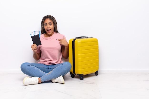 Giovane donna afro che si sente felice, sorpresa e orgogliosa, indicando se stessa con uno sguardo eccitato e stupito. concetto di vacanze
