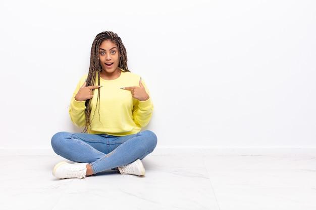 Giovane donna afro che si sente felice, sorpresa e orgogliosa, indicando se stessa con uno sguardo eccitato e stupito