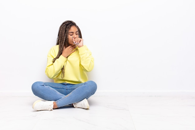 Giovane donna afro che si sente male con mal di gola e sintomi influenzali, tosse con la bocca coperta