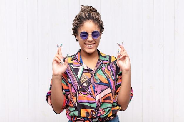 Giovane donna afro che si sente nervosa e piena di speranza, incrociando le dita
