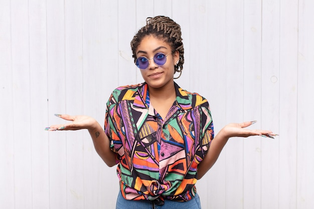Giovane donna afro sentirsi perplessa e confusa, dubitando, ponderando o scegliendo diverse opzioni con un'espressione divertente