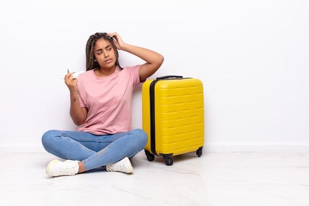 Giovane donna afro che si sente perplessa e confusa, grattandosi la testa e guardando di lato. concetto di vacanze