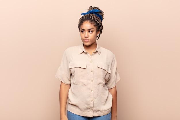 Giovane donna afro che si sente triste, arrabbiata o arrabbiata e guarda al lato