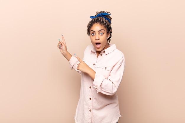 Giovane donna afro sentirsi scioccata e sorpresa, indicando