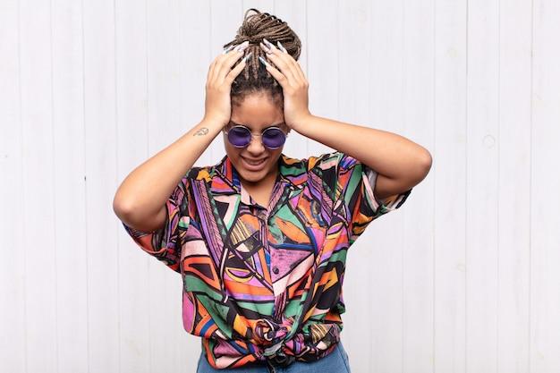 Giovane donna afro che si sente stressata e frustrata, alza le mani alla testa, si sente stanca, infelice e con emicrania