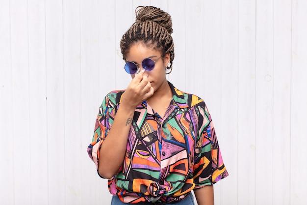 Giovane donna afro che si sente stressata, infelice e frustrata, si tocca la fronte e soffre di emicrania di forte mal di testa