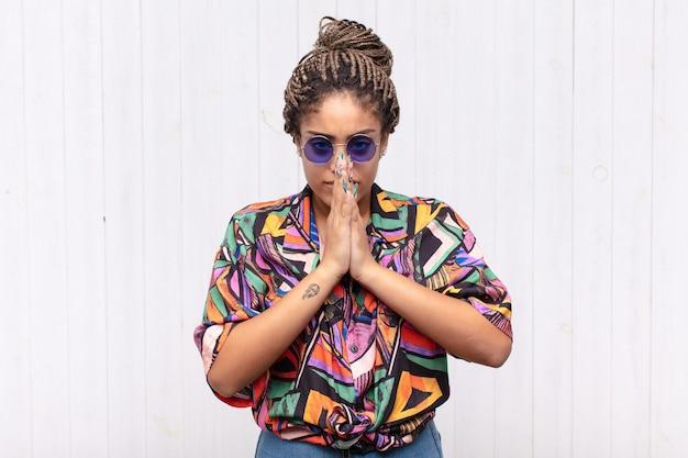 Giovane donna afro che si sente preoccupata, fiduciosa e religiosa, pregando fedelmente con i palmi premuti, chiedendo perdono