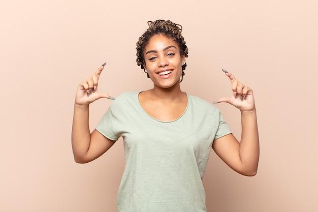 Giovane donna afro che inquadra o delinea il proprio sorriso con entrambe le mani, guardando positivo e felice, concetto di benessere