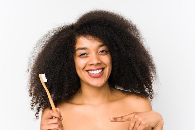 Giovane donna afro che tiene uno spazzolino da denti isolato sorridendo allegramente indicando con l'indice lontano