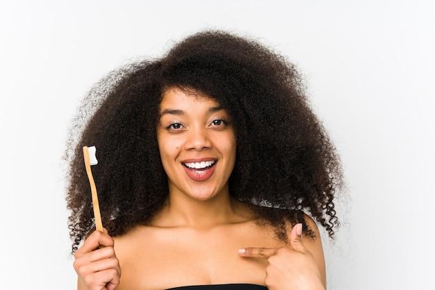 Giovane donna afro che tiene uno spazzolino da denti isolato sorpreso indicando se stesso, sorridendo ampiamente.