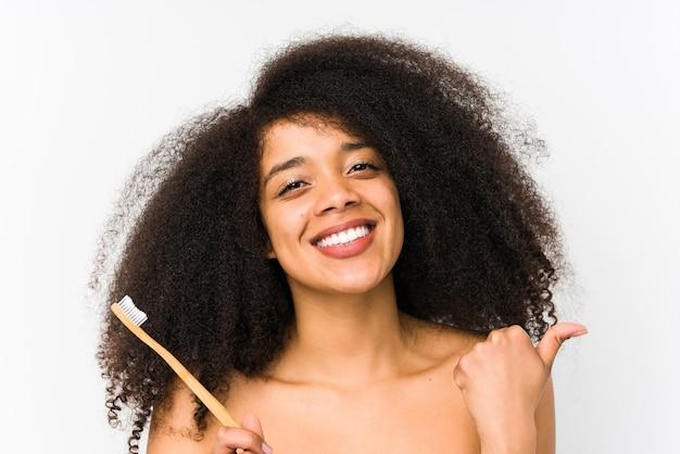 Giovane donna afro che tiene uno spazzolino da denti