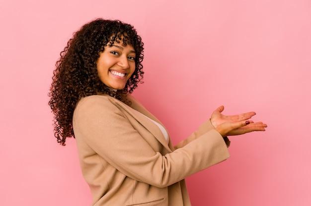 Giovane donna afro isolata che tiene uno spazio della copia su una palma