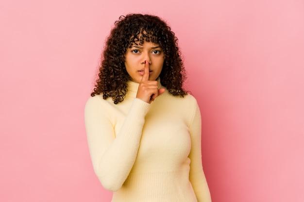 Giovane donna afro isolata mantenendo un segreto o chiedendo il silenzio