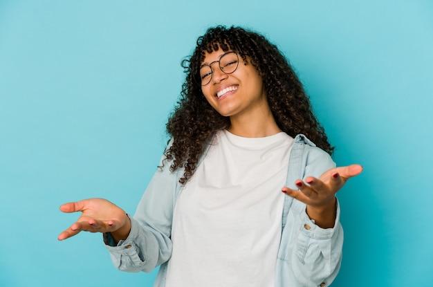Giovane donna afro isolata che mostra un'espressione di benvenuto