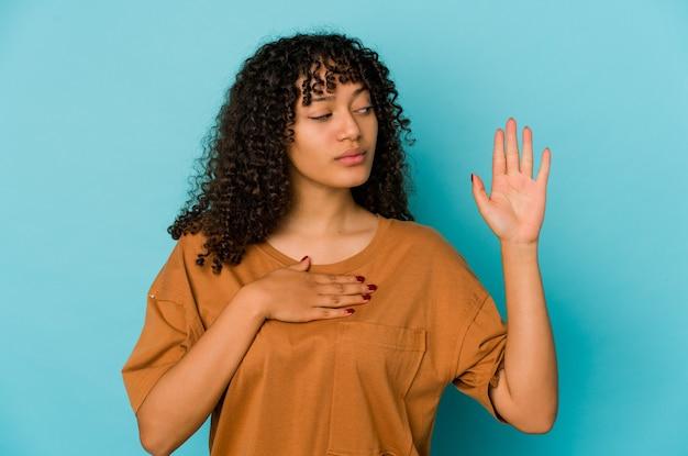 Giovane donna afro isolata prestando giuramento, mettendo la mano sul petto