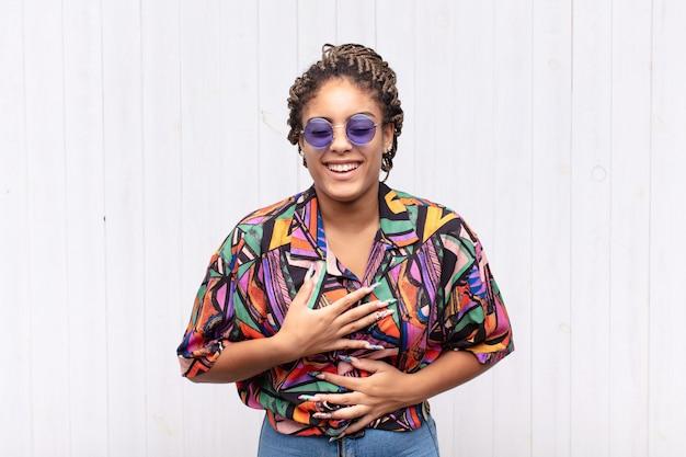 Giovane donna afro che ride ad alta voce a qualche divertente scherzo isolato