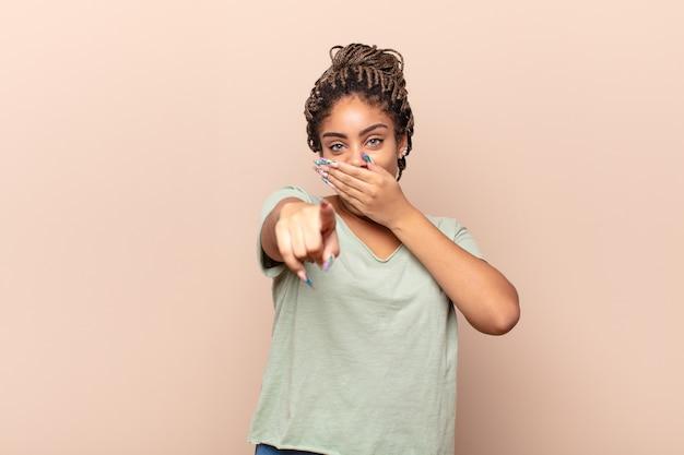 Giovane donna afro che ride di te, indica la telecamera e ti prende in giro o ti prende in giro