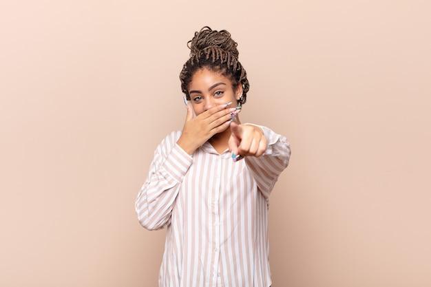 Giovane donna afro che ride di te, indica e ti prende in giro o ti prende in giro