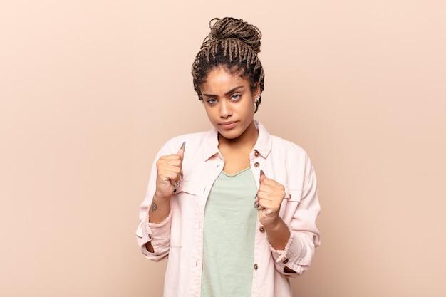 Giovane donna afro che sembra sicura, arrabbiata, forte e aggressiva, con i pugni pronti a combattere in posizione di boxe