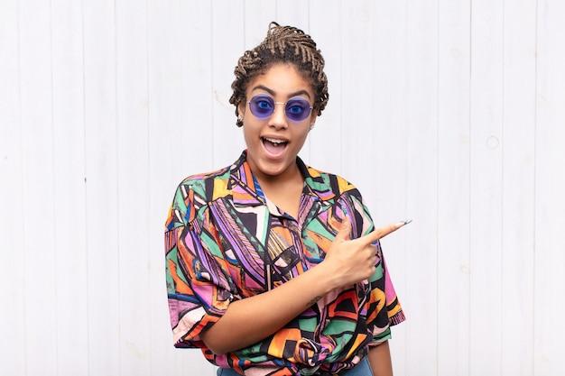 Giovane donna afro che sembra eccitata e sorpresa che punta di lato e verso l'alto