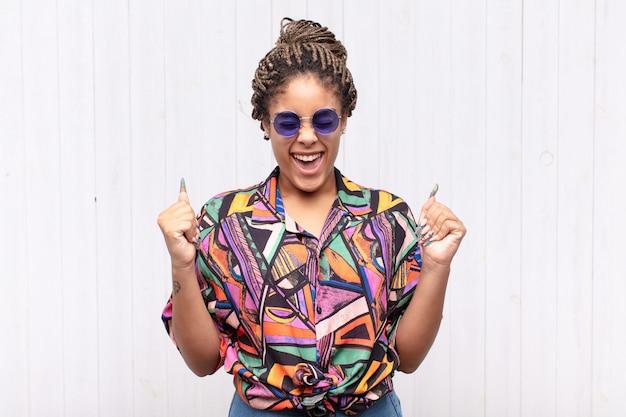 Giovane donna afro che sembra estremamente felice e sorpresa, celebrando il successo, gridando e saltando