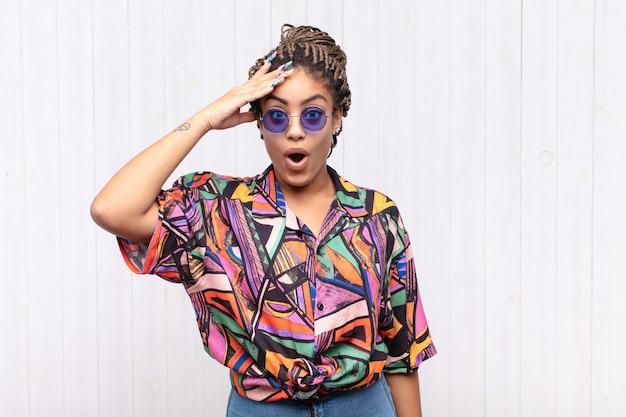 Giovane donna afro che sembra felice, stupita e sorpresa, sorridente e realizzando incredibili e incredibili buone notizie