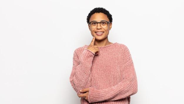 Giovane donna afro che sembra felice e sorridente con la mano sul mento, chiedendosi o facendo una domanda, confrontando le opzioni