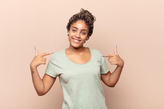 Giovane donna afro che sembra orgogliosa, arrogante, felice, sorpresa e soddisfatta, indicando se stessa, sentendosi come una vincitrice