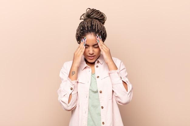 Giovane donna afro che sembra stressata e frustrata, lavora sotto pressione con un mal di testa e tormentata dai problemi
