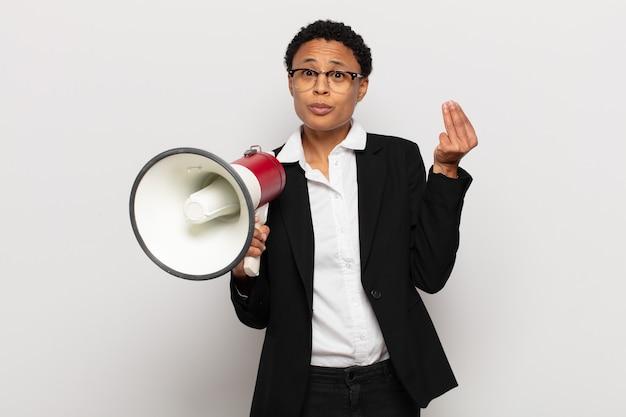 Giovane donna afro che fa capice o gesto di denaro, dicendoti di pagare i tuoi debiti!