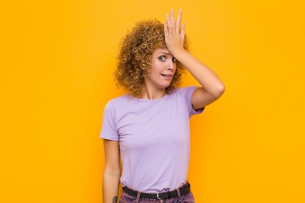 Giovane donna afro che solleva il palmo sulla fronte pensando oops, dopo aver fatto uno stupido errore o aver ricordato, sentendosi muto contro il muro arancione